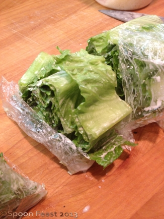 Slice the lettuce with the plastic wrap still on. Of course, remove it as you bring the lettuce to the plate.